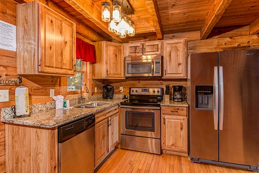 Kitchen with stainless steel appliances at Cupid's Crossing, a 1-bedroom cabin rental located in Pigeon Forge
