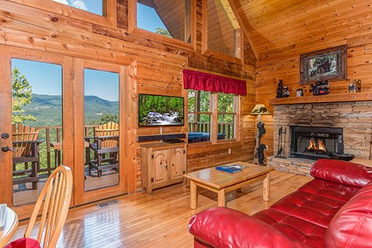 Living room with large windows overlooking the mountains at Cupid's Crossing, a 1-bedroom cabin rental located in Pigeon Forge