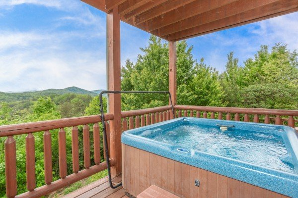 Hot tub on a covered deck at Mountain Bliss, a 2 bedroom cabin rental located in Pigeon Forge