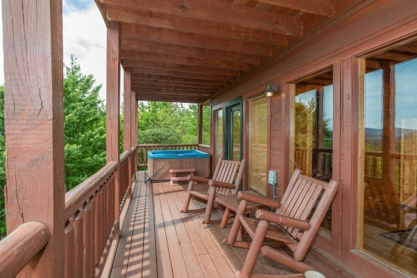Log rocking chairs and a hot tub on a covered deck at Mountain Bliss, a 2 bedroom cabin rental located in Pigeon Forge