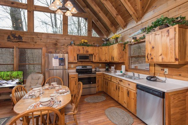 Kitchen with stainless appliances and dining space for four at Moose Tracks, a 1 bedroom cabin rental located in Gatlinburg