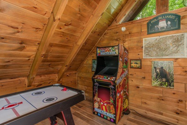 Air hockey and an arcade game at Moose Tracks, a 1 bedroom cabin rental located in Gatlinburg