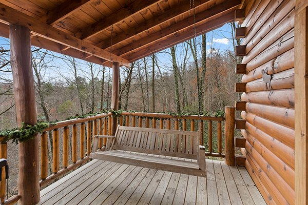 Porch swing on the covered deck at Moose Tracks, a 1 bedroom cabin rental located in Gatlinburg