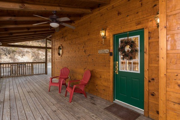 Adirondack chairs near the front door on the covered deck at Alone Time, a 1 bedroom cabin rental located in Pigeon Forge