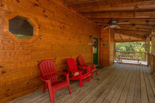Covered porch with red Adirondack chairs at Alone Time, a 1 bedroom cabin rental located in Pigeon Forge