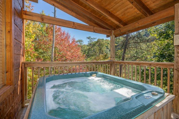 Hot tub on a covered deck at Alone Time, a 1 bedroom cabin rental located in Pigeon Forge