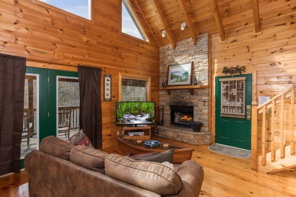 Living room with stone fireplace and television at Alone Time, a 1 bedroom cabin rental located in Pigeon Forge