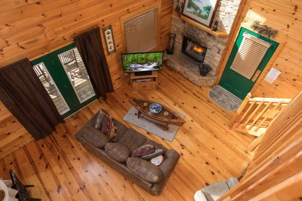 Overhead view of the living room with stone fireplace at Alone Time, a 1 bedroom cabin rental located in Pigeon Forge