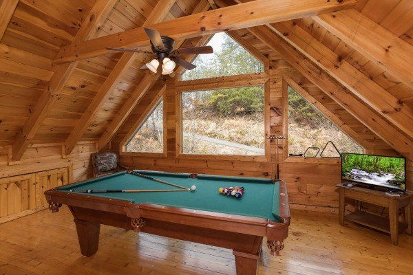 Pool table and television in the loft at Alone Time, a 1 bedroom cabin rental located in Pigeon Forge