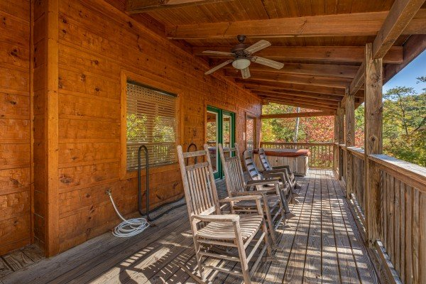 Rocking chairs on a covered deck at Alone Time, a 1 bedroom cabin rental located in Pigeon Forge