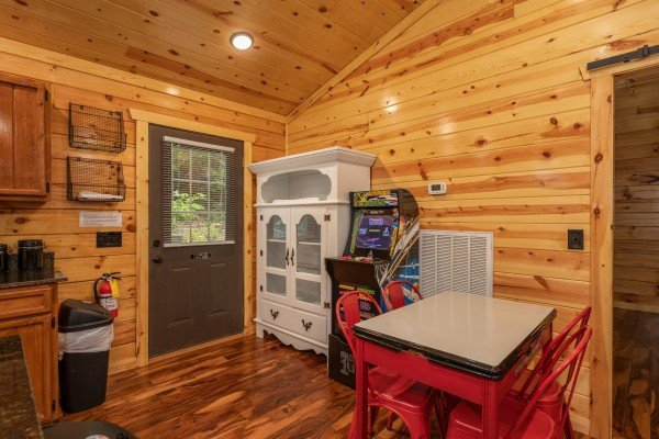 Dining space with hutch and arcade game at Paws on the Porch, a 2 bedroom cabin rental located in Gatlinburg