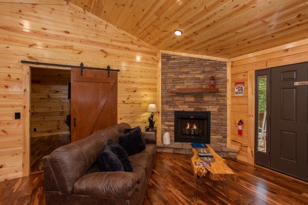 Fireplace and sliding barn door in the living room at Paws on the Porch, a 2 bedroom cabin rental located in Gatlinburg