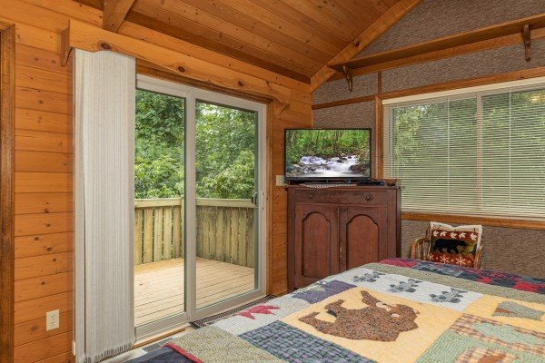 TV and deck access in a bedroom at Cubs' Crib, a 3 bedroom cabin rental located in Gatlinburg