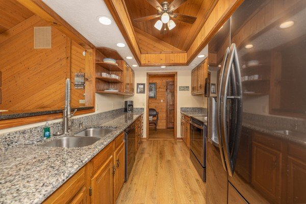 Galley kitchen with granite counters and black appliances at Cubs' Crib, a 3 bedroom cabin rental located in Gatlinburg