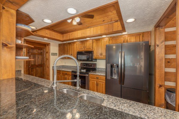 Kitchen with black appliances at Cubs' Crib, a 3 bedroom cabin rental located in Gatlinburg
