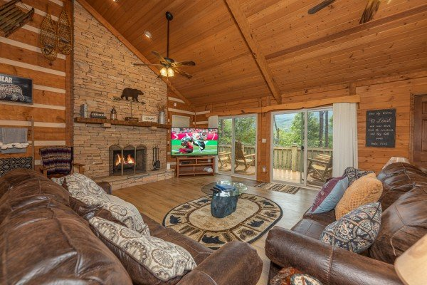 Living room with fireplace, TV, and deck access at Cubs' Crib, a 3 bedroom cabin rental located in Gatlinburg