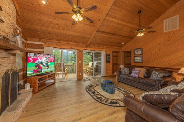 Living room with TV, fireplace, and deck access at Cubs' Crib, a 3 bedroom cabin rental located in Gatlinburg