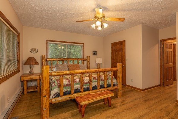 Bedroom with a log bed, two night stands, and a bench at Cubs' Crib, a 3 bedroom cabin rental located in Gatlinburg