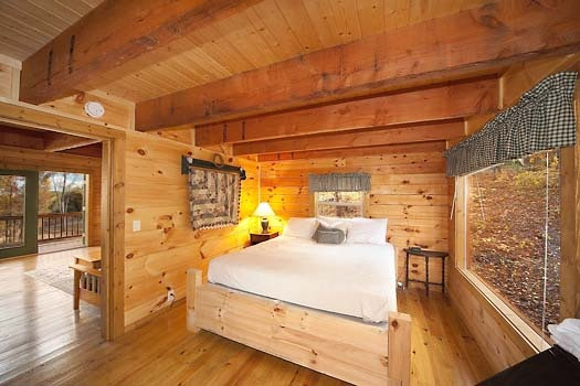 king sized bed in bedroom at licklog hollow a 1 bedroom cabin rental located in pigeon forge