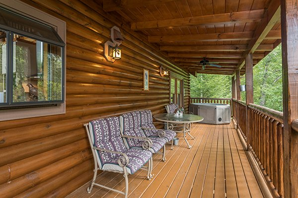 Outdoor dining set near the hot tub on the covered deck at Laid Back, a 2 bedroom cabin rental located in Pigeon Forge