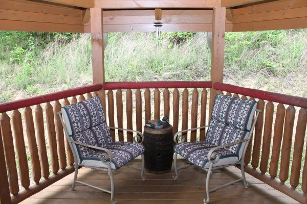Two chairs and a small table on the covered deck at Laid Back, a 2 bedroom cabin rental located in Pigeon Forge