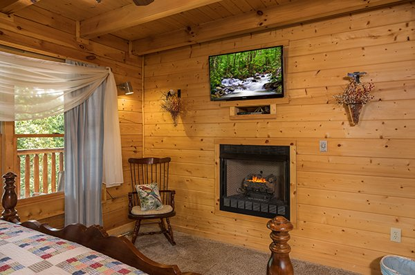 Bedroom with a TV and fireplace at Laid Back, a 2 bedroom cabin rental located in Pigeon Forge
