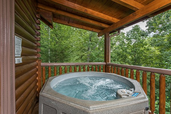 Hot tub on a covered deck surrounded by trees at Laid Back, a 2 bedroom cabin rental located in Pigeon Forge