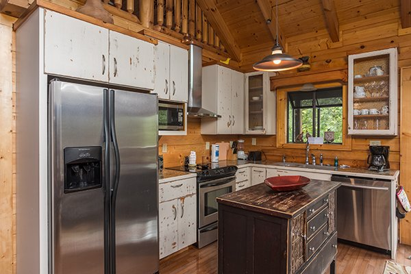 Kitchen with white cabinets and stainless steel appliances at Laid Back, a 2 bedroom cabin rental located in Pigeon Forge