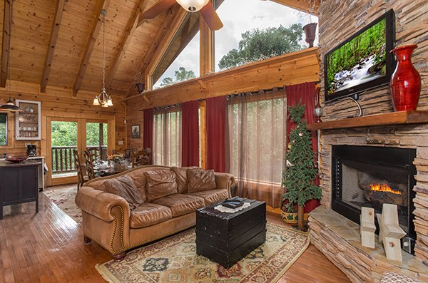 Living room with vaulted ceiling and large windows at Laid Back, a 2 bedroom cabin rental located in Pigeon Forge