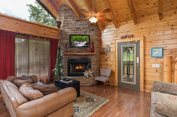 Fireplace and television in a living room with vaulted ceiling at Laid Back, a 2 bedroom cabin rental located in Pigeon Forge