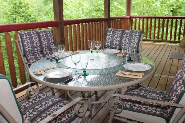 Outdoor dining set for four on the covered deck at Laid Back, a 2 bedroom cabin rental located in Pigeon Forge