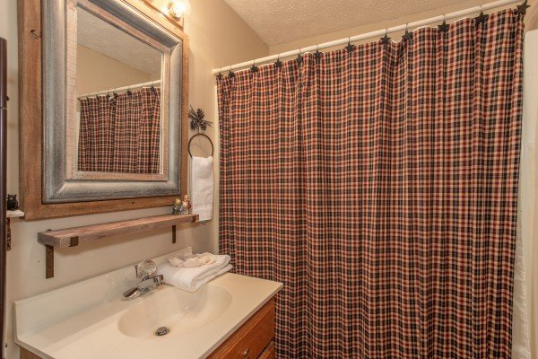 Bathroom with a tub and shower at Black Bear Holler, a cabin rental in Pigeon Forge
