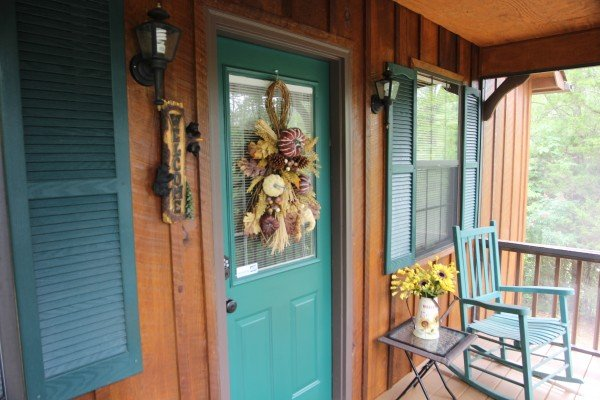 Front porch with fall-themed decor and a rocking chair at Black Bear Holler, a 2-bedroom cabin rental located in Pigeon Forge