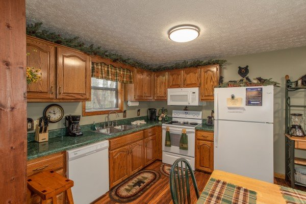 Kitchen with white appliances at Black Bear Holler, a cabin rental in Pigeon Forge