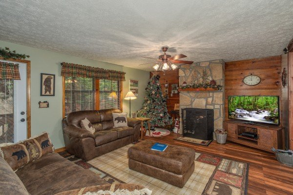 Living room with fireplace and TV at Black Bear Holler, a cabin rental in Pigeon Forge
