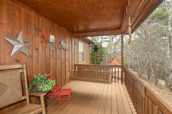 Swing on a covered porch at Black Bear Holler, a cabin rental in Pigeon Forge