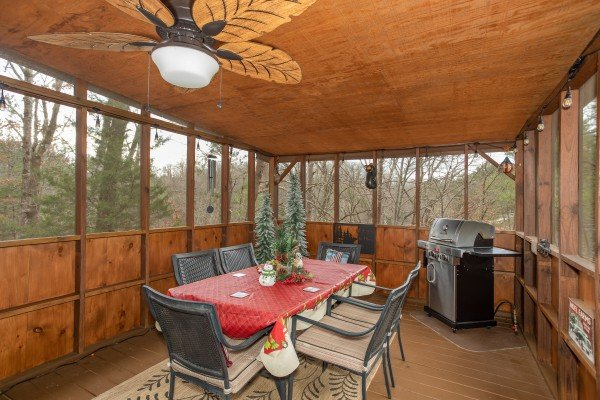 Dining for six and propane grill on a screened deck at Black Bear Holler, a cabin rental in Pigeon Forge