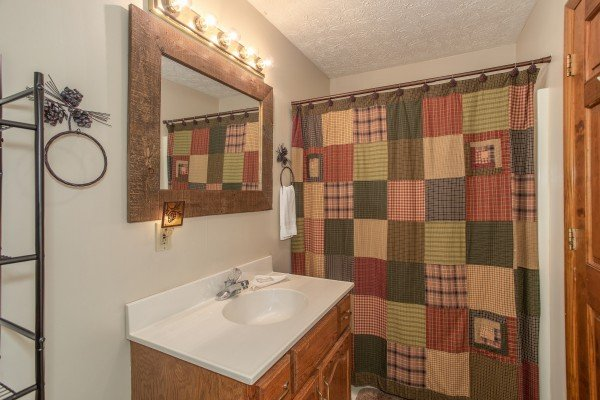 Bathroom with tub and shower at Black Bear Holler, a cabin rental in Pigeon Forge