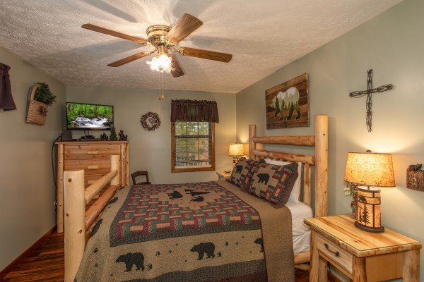 Bedroom with a queen bed, TV, and dresser at Black Bear Holler, a cabin rental in Pigeon Forge