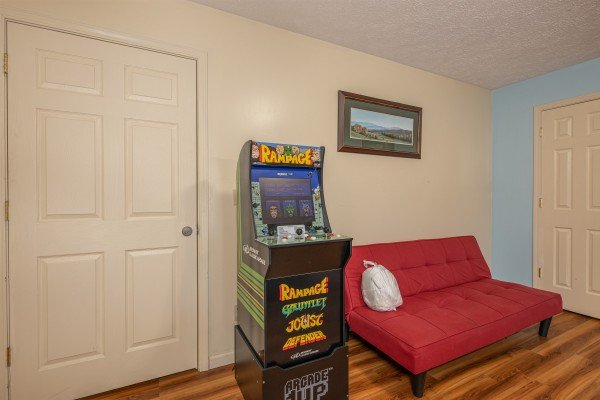 Arcade game and futon at Pampered Campers, a 3 bedroom cabin rental located in Pigeon Forge