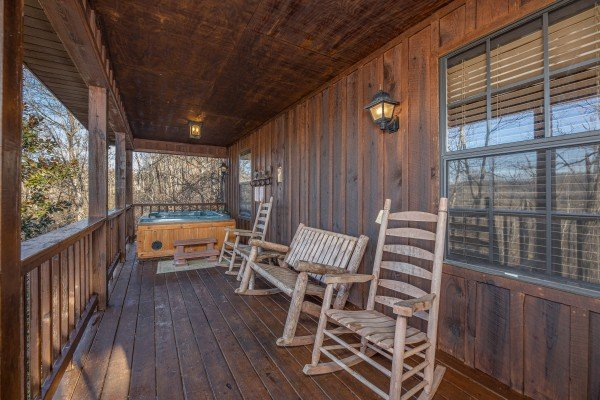 Hot tub and rocking chairs on a deck at Pamepered Campers, a 3 bedroom cabin rental in Pigeon Forge