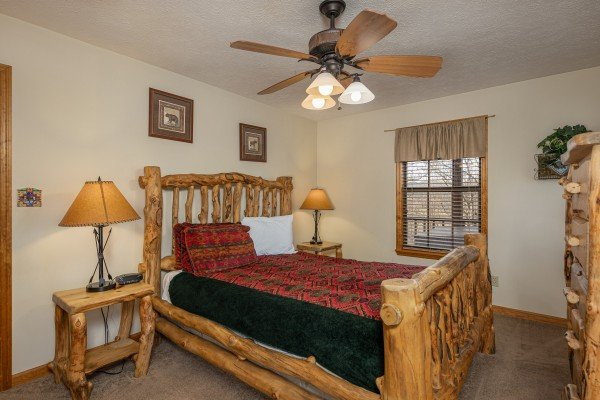 Bedroom with a log bed, two night stands, lamps, and a dresser at Pampered Campers, a 3 bedroom cabin rental located in Pigeon Forge