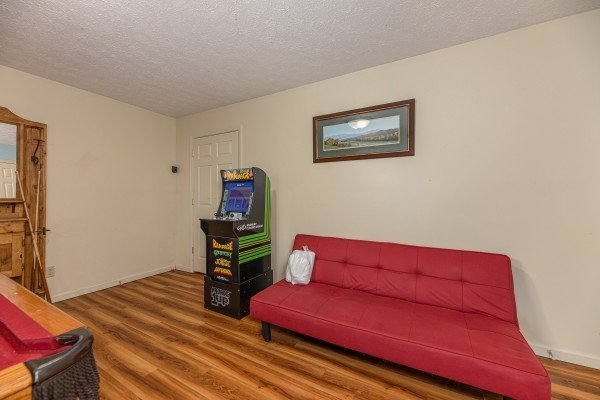 Game room with arcade game, futon, and pool table at Pampered Campers, a 3 bedroom cabin rental located in Pigeon Forge