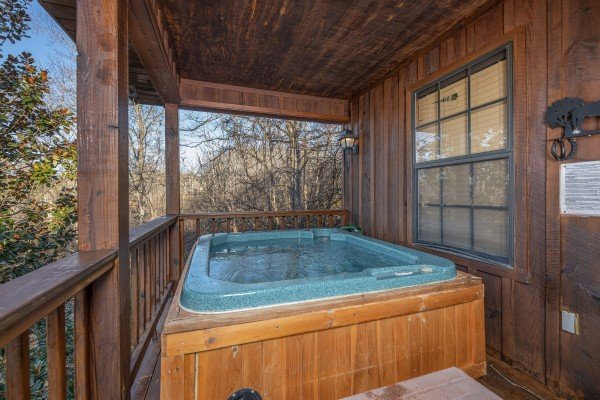 Hot tub on a covered deck at Pampered Campers, a 3 bedroom cabin rental in Pigeon Forge