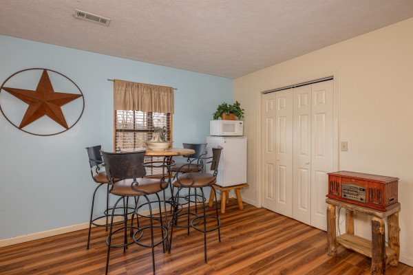 Kitchenette with high table and four stools at Pampered Campers, a 3 bedroom cabin rental located in Pigeon Forge