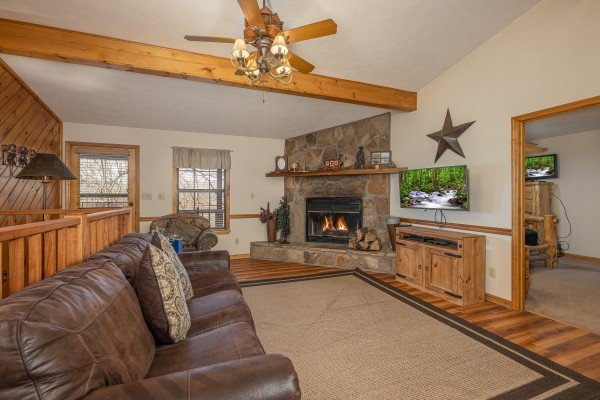 Living room with wood burning fireplace at Pampered Campers, a 3 bedroom cabin rental located in Pigeon Forge