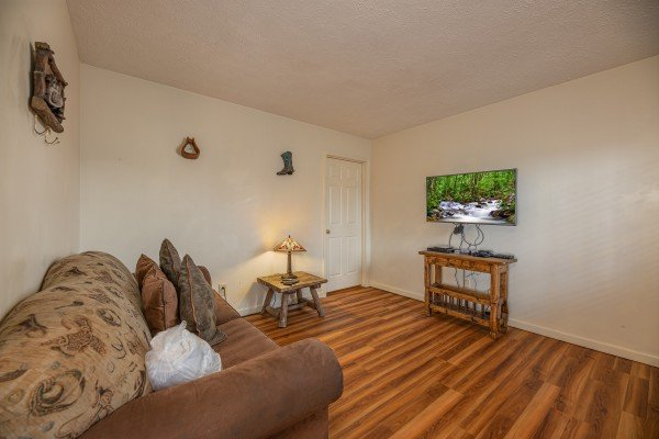 Downstairs living area with sofa and TV at Pampered Campers, a 3 bedroom cabin rental located in Pigeon Forge