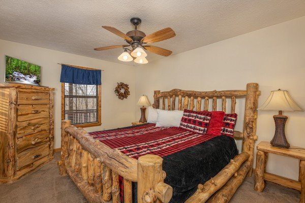 Bedroom with a log bed, two night stands, lamps, dresser, and TV at Pampered Campers, a 3 bedroom cabin rental located in Pigeon Forge