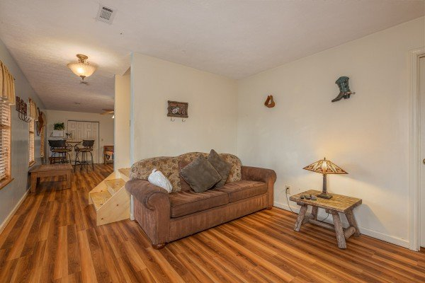 Sofa in the game area at Pampered Campers, a 3 bedroom cabin rental located in Pigeon Forge