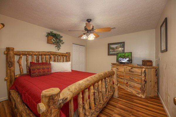 Bedroom with a log bed, dresser, and TV at Pampered Campers, a 3 bedroom cabin rental located in Pigeon Forge